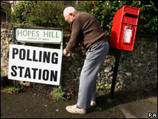A man putting up a sign for a polling station
