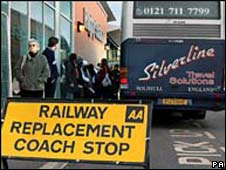 Rail passengers await coaches at Rugby