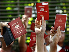 Pro-democracy Burmese citizens raise their passports outside the embassy in Singapore as they vote early in the referendum on 27 April