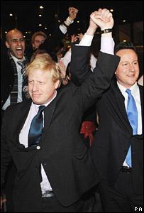 El líder del Partido Conservador, David Camerón, levanta la mano al victorioso Johnson