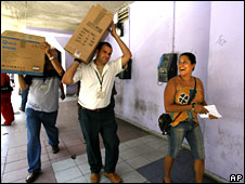Cuban computer shop employees carry computer to customer's car