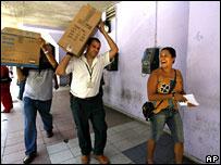 عمال محل كمبيوتر كوبي يحملون اجهزة كومبيوتر