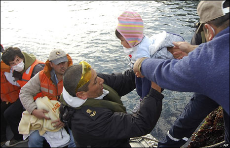 A Navy soldier hands a child onto a waiting boat to be evacuated out of Chaiten, southern Chile 2/05/08
