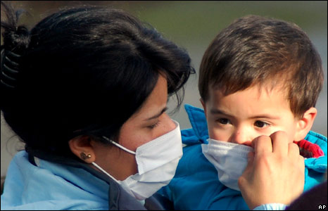 A woman puts a mask on her son to protect against volcano ash in Chaiten, Chile 2/05/08