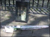 Una vela encendida y un ramo de rosas en memoria de Madeleien, en Rothley