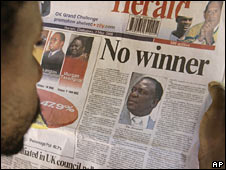 A Zimbabwean reads the state-owned daily The Herald in Harare, 3 May 2008.