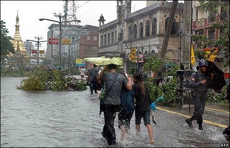 People walk through a flooded Rangoon street on 3 May