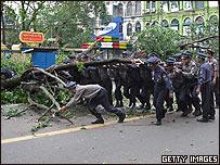 Policías birmanos retiran un árbol derribado por el ciclón