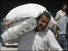 A Palestinian man carries sacks of food aid in the Gaza Strip - 24/4/2008