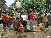 Mujeres de Rangún se acercan a un pozo a sacar agua