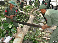 Soldiers use a hand-saw to cut down a tree blocking a road, 5th May