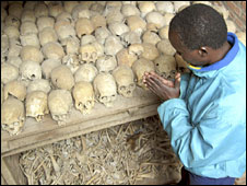 Rwanda genocide survivor praying next to skulls (file picture)