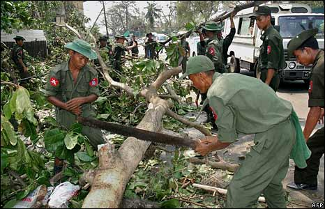 Soldiers saw a tree blocking a street in Rangoon