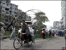 A bike taxi driver moves through a damaged area of Rangoon on 4 May 2008