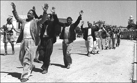 Palestinians march with raised hands during the surrender of the town of Ramle, in May 1948