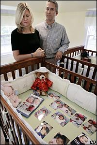 Una pareja estadounidense frente a fotos de bebés guatemaltecos.