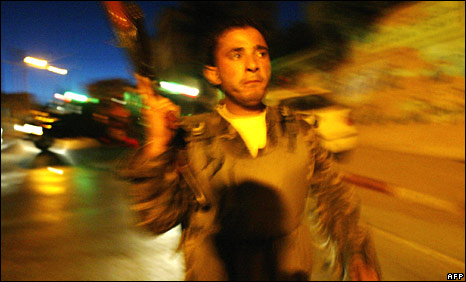 A Palestinian policeman outside the government building after it was set on fire in 2006 during Palestinian factional rivalry