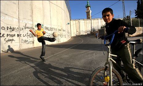 Palestinian boys play under Israel's separation barrier in May 2008