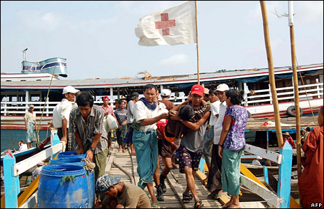 Locals rush an injured person to emergency workers in the Irrawaddy river delta region (5 May 2008)