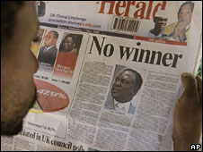 "A Zimbabwean reads the Herald newspaper with a headline: ""No winner"""
