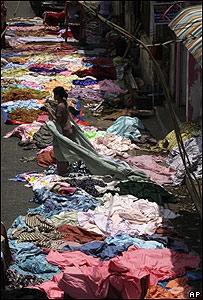 Mujer seca su ropa en las afueras de un mercado, AP