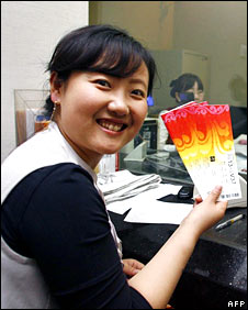 Chinese woman smiles as she holds up her Olympic tickets
