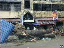 residents of Rangoon walk past fallen trees Tuesday, May 6, 2008, following cyclone Nargis