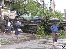 people walk past fallen trees at a street in Rangoon