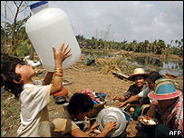 Un ni�o ebeb agua de un bid�n mientras su familia disfruta de la comida donada