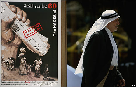 Palestinian man walks past a poster commemorating the Nakba