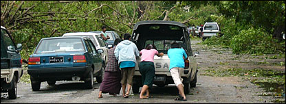 People pushing a car along a road in Rangoon after cyclone Nargis