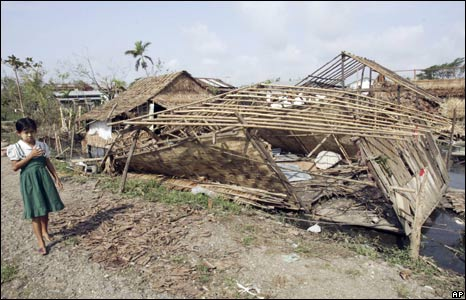 A girl stands next to a house on the outskirts of Rangoon damaged by Cyclone Nargis, 8 May 2008
