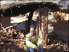 Farm-worker in damaged hut