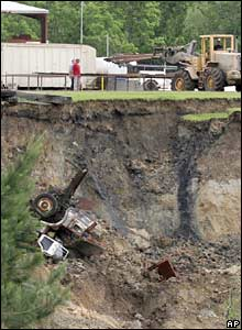 A truck falls into sinkhole as a tractor is used to remove other equipment from the site 7 May  2008