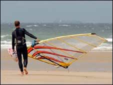 A windsurfer on a beach