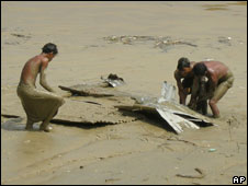 Men work to salvage a steel roof from the mud on the banks of the Rangoon River