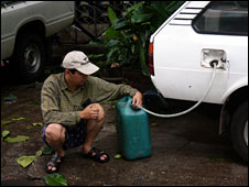 A man draining petrol from his car in Rangoon