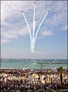 "Israelis gather on the beach in Tel Aviv as they watch Israeli jets ""Fuga Magister"" performing during a military parade marking Israel's 60th anniversary on May 8, 2008"