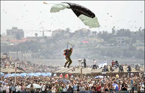 A paratrooper prepares to land on the beach during a aerial display to mark the 60th anniversary of Israel