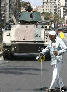 A Lebanese elderly man crosses a street past a Lebanese soldier sitting atop an armoured personnel carrier in Beirut's Corniche al-Mazraa district on May 8, 2008.