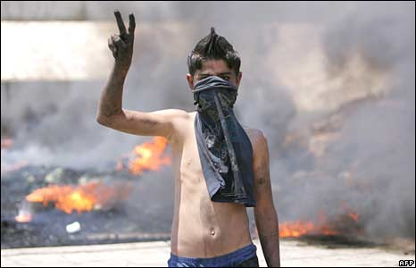 Smoke billows from burning tyres as a Lebanese boy flashes the victory sign at a blocked road leading to Rafiq Hariri International Airport in Beirut on 8 May, 2008.