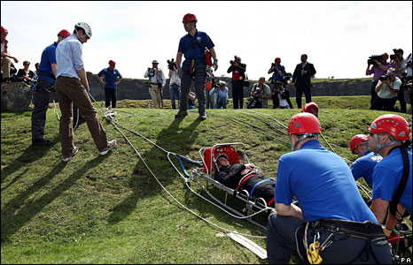 Prince William (left, white helmet) pulls a rope as a casualty is lowered down a 200ft cliff at Morlais Quarry near Merthyr.