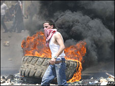 A man burns tires to block a highway near Beirut on 8 May 2008