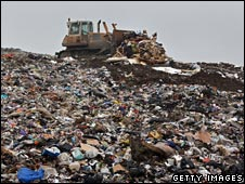 A bulldozer moves landfill rubbish