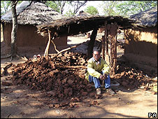 A farm labourer sits on the remains of his demolished hut in Umguzaan Farm in Nyamandhlovu, north of Bulawayo