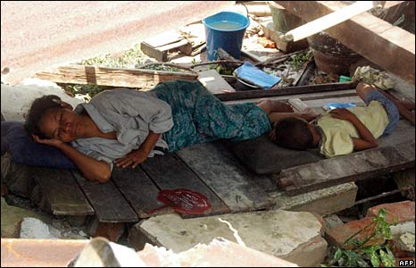 A displaced woman sleeps on a piece of wood in Bogalay on 8 May 2008
