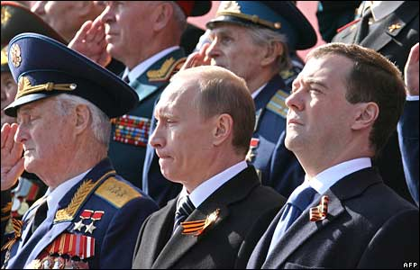 Russian President Dmitry Medvedev (R) and Prime Minister Vladimir Putin (C) sit with WWII veterans during a Victory Day Parade on Red Square in Moscow