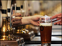 Pint of beer on a bar with beer pumps. c/o Getty images