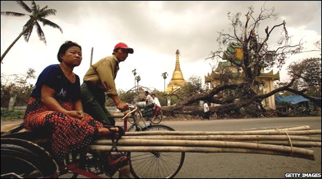 People ride a bike past an uprooted tree on May 8, 2008 in downtown Yangon, Burma