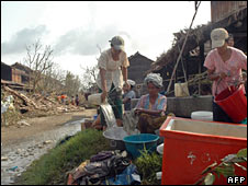People clean their belongings along a street in Kungyangon, near Rangoon. Photo: 8 May 2008